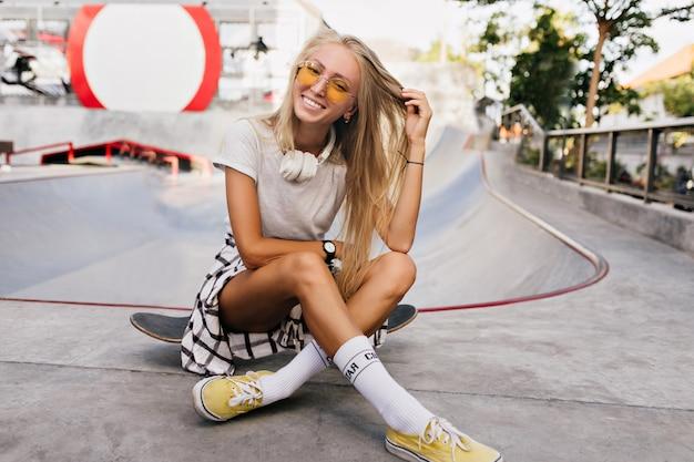 Adorabile donna pattinatrice che gioca con i suoi capelli biondi. ritratto all'aperto della splendida modella femminile in scarpe gialle che si siede sullo skateboard.