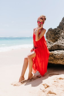 石の上に座っている夏のアクセサリーを持つ愛らしい日焼けした若い女性。休暇中に野生のビーチで休んでいる興奮した女の子の屋外ショット。