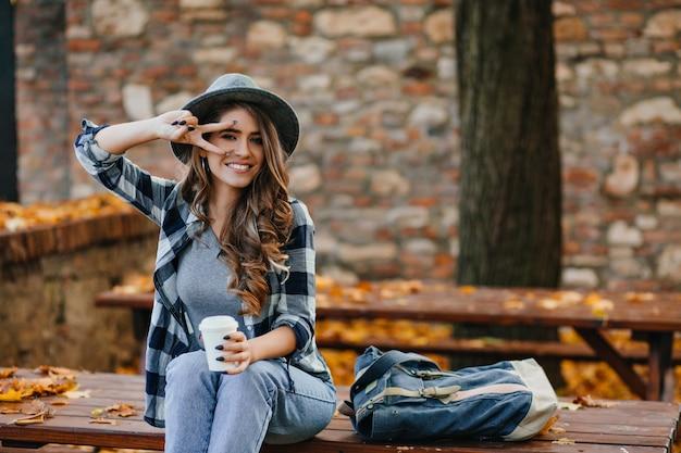 공원에서 커피를 마시면서 평화의 한숨을 쉬며 포즈를 취하는 곱슬 헤어 스타일로 사랑스러운 백인 여성 모델