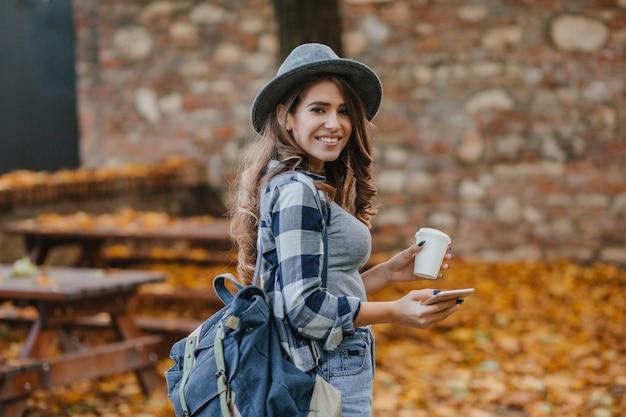 Amabile ragazza bianca in camicia a scacchi che tiene smartphone e tazza di caffè nel parco di settembre