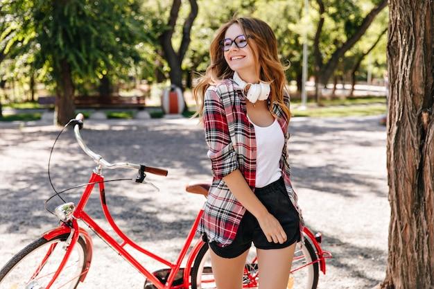 自転車の近くでポーズをとる黒のショートパンツで愛らしい女性。夏の公園で楽しんでいる熱狂的な白人女性の屋外写真。