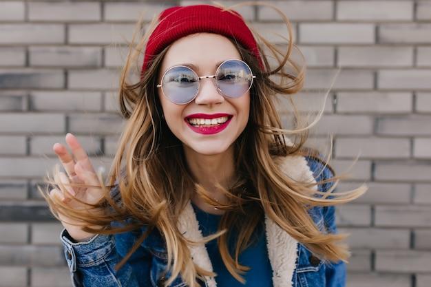 야외 촬영 중에 장난하는 캐주얼 파란색 안경에 사랑스러운 여자. 벽돌 벽에 포즈 밝은 화장과 흥분된 금발 소녀의 초상화.