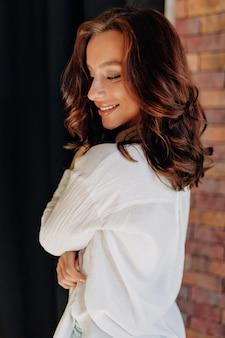 黒髪の日焼けした肌と白いシャツを着た素敵な笑顔の愛らしい女性優しい笑顔と顔を覆う