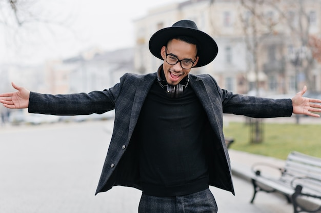 Lovable young man with brown skin waving hands on city street. outdoor portrait of stylish african guy in headphones posing emotionally in spring park.