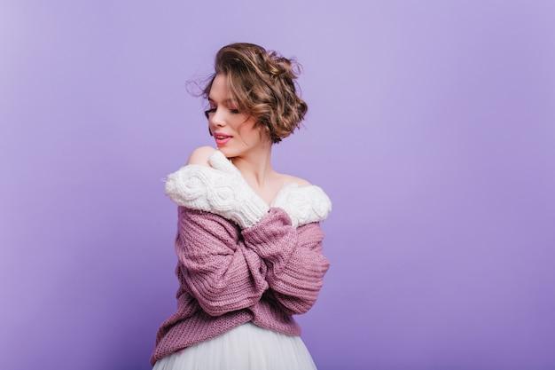 Amabile giovane donna in graziosi guanti bianchi in piedi con gli occhi chiusi. ritratto di ragazza affascinante dai capelli corti in guanti di lana isolati sulla parete viola.