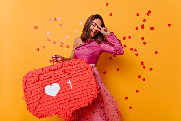 Очаровательная молодая женщина в розовой блузке танцует от счастья. снимок потрясающей женщины-блогера улыбается в помещении