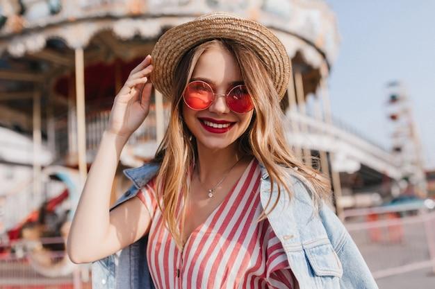 좋은 여름 날에 포즈 세련 된 핑크 선글라스에 사랑스러운 젊은 여자. 봄 아침에 놀이 공원에서 놀아요 로맨틱 여성 모델의 야외 초상화.