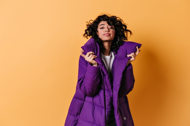 Lovable young woman posing in purple down jacket