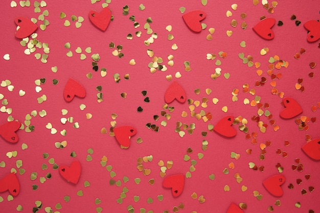 Love abstract red background with golden heart shaped glitter. valentine's day flat lay.