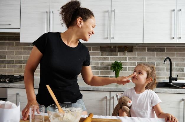 愛、愛情、優しさ、家族関係。ママは小麦粉で彼女の指で娘の鼻に触れます。母と娘が一緒に生地を準備します。