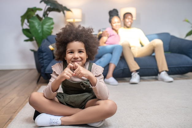 Love. african american little smiling girl showing heart with fingers sitting on floor and happy parents on sofa behind