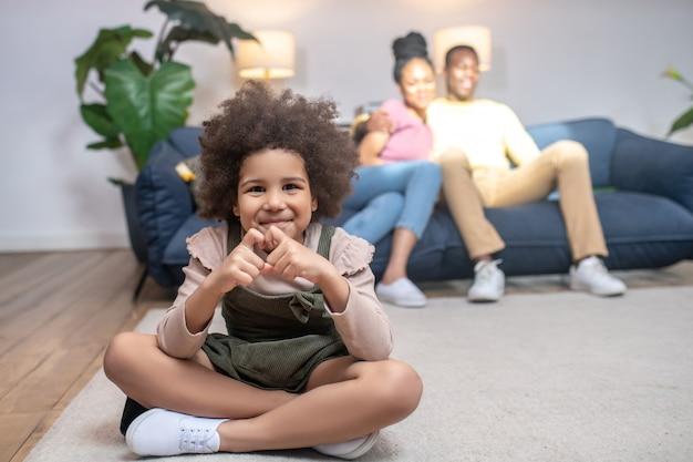 사랑. 바닥에 앉아 있는 손가락과 소파 뒤에 있는 행복한 부모와 함께 마음을 보여주는 아프리카계 미국인 미소 짓는 소녀