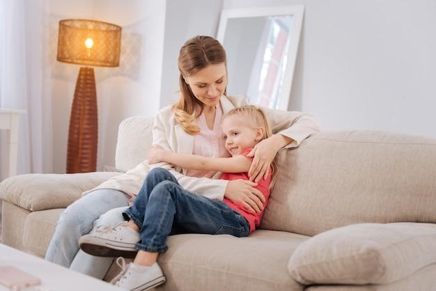 사랑과 보살핌. 긍정적 인 좋은 젊은 여자가 소파에 앉아 그녀의 사랑과 관심을 표현하면서 그녀의 딸을 포옹 프리미엄 사진