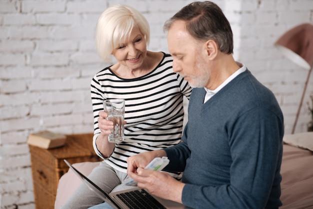 사랑과 보살핌. 그의 사랑하는 아내가 그를 위해 물 잔을 들고있는 동안 케이스에서 약을 복용하려고하는 노인의 측면보기.