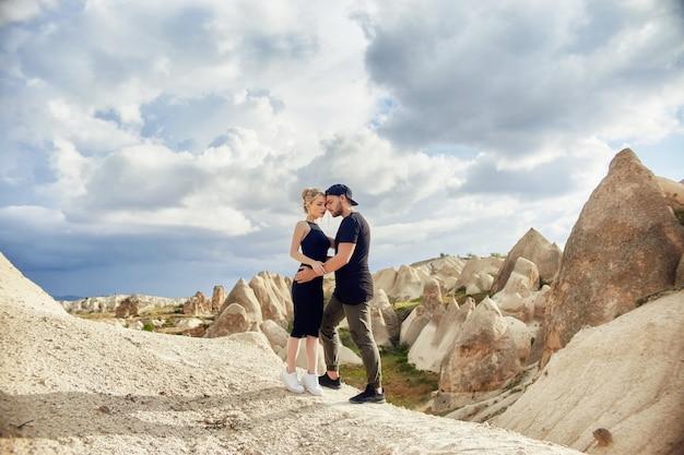 Любовь и эмоции влюбленная пара отдыхает в турции. влюбленные восточные пары в горах каппадокии обнимаются и целуются. крупным планом портрет мужчины и женщины. красивые серьги полумесяца на ушах девушки