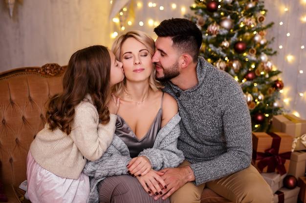 クリスマスツリーの近くで幸せなお母さんにキスする愛と家族の概念の父と娘