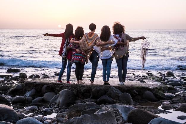 Концепция любви и дружбы с группой женщин, вместе наслаждающихся закатом на берегу океана -