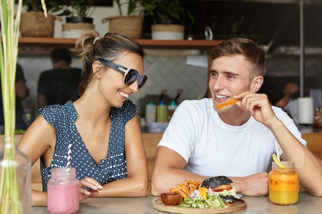 愛と友情。フライドポテトとハンバーガーを食べて、居心地の良いカフェテリアでデート中に新鮮な飲み物を持っている幸せなカップル。彼女のボーイフレンドのジョークを聞いて笑っているトレンディなサングラスでかわいい女性