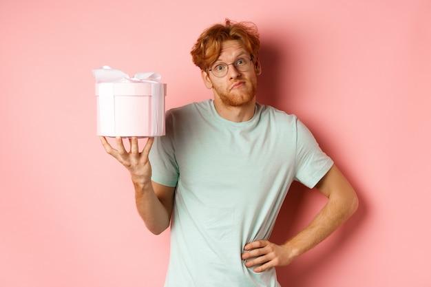 愛と休日のコンセプト面白い赤毛の男は愚かな肩をすくめて、バレンタインのためのピンクのギフトボックスを示しています...