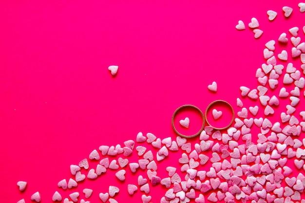 사랑과 결혼 개념. 발렌타인 데이. 복사 공간 밝은 분홍색 배경에 작은 밝은 분홍색 마음 가운데 누워 두 황금 결혼 반지
