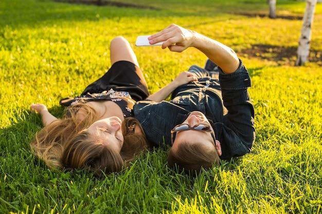 사랑과 사람 개념입니다. 여름에 잔디에 누워 셀카를 찍는 행복한 10대 커플.