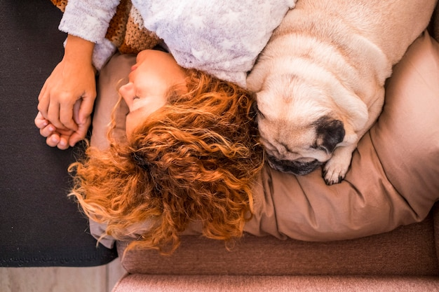 Любовь и защита и лучшие друзья навсегда концепция с красивой кавказской женщиной, спящей рядом со своим прекрасным щенком-мопсом - дружба сверху вертикального вида