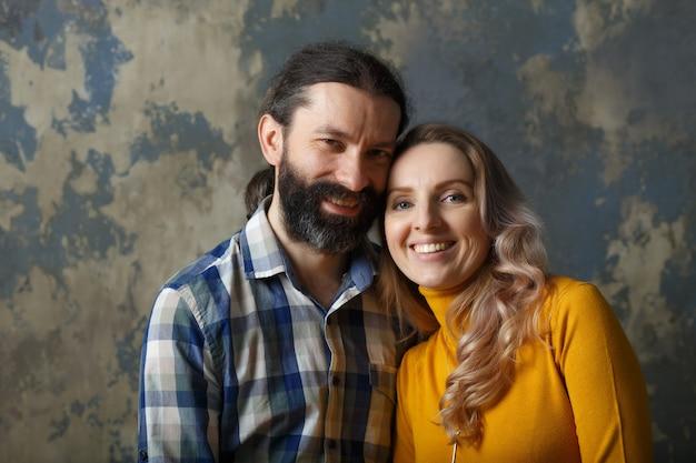 愛と関係の概念。抱き締めて、大きく笑って、カメラを見て、青い抽象的な背景の上に一緒に立っている幸せな大人のカップル