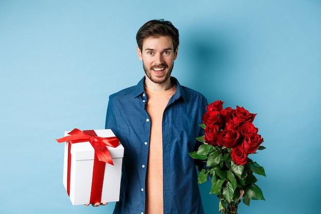사랑과 관계 개념. 행복 한 젊은 남자는 낭만적 인 데이트에 꽃과 선물을 가져옵니다. 남자 친구는 장미 꽃다발과 파란색 배경에 현재 서를 기원합니다.