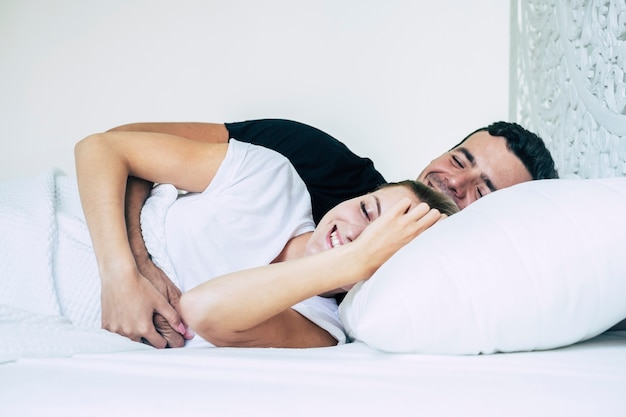 행복과 미소와 함께 흰색 침실과 침대에서 자고있는 젊은 부부와 사랑과 관계 개념