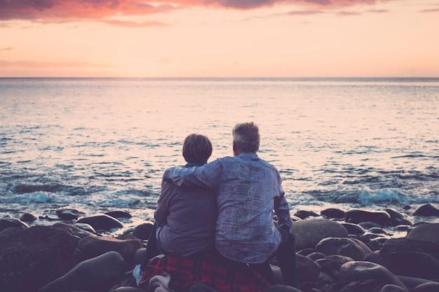 大人との愛とロマンスは成熟します-日没のリラックスした海を見ながら座って抱き合っている老夫婦。休暇、余暇、リラクゼーションの概念-