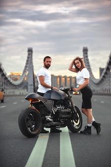 사랑과 낭만적 인 개념. 오토바이의 아름다운 커플은 다리 위의 도로 한가운데서 서로 마주보고 있습니다.