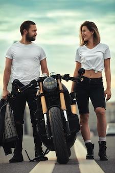 사랑과 낭만적인 개념입니다. 오토바이를 탄 아름다운 부부는 다리 위 도로 한가운데서 서로 마주보고 서 있습니다.