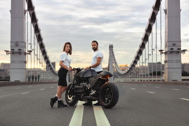 Любовь и романтическая концепция. красивая пара на мотоцикле стоит друг напротив друга посреди дороги на мосту, на двойном твердом теле.
