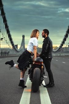 Любовь и романтическая концепция. красивая пара на мотоцикле стоит друг напротив друга посреди дороги на мосту