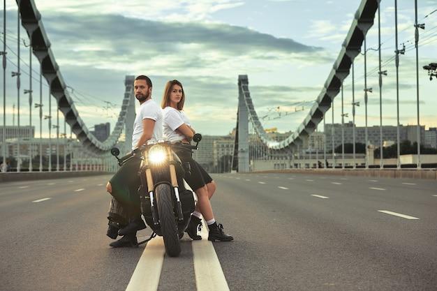 Любовь и романтическая концепция. красивая пара на мотоцикле стоит друг напротив друга посреди дороги