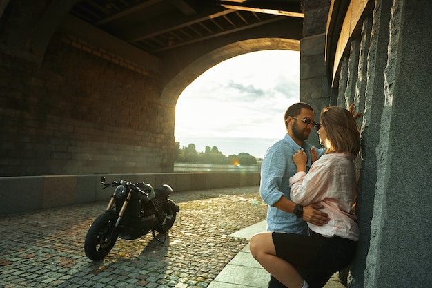 Любовь и романтическая концепция. влюбленная пара на закате стоит у стены, целуется и обнимается под мостом рядом с мотоциклом. мужчина с бородой обнимает женщин, нежность.