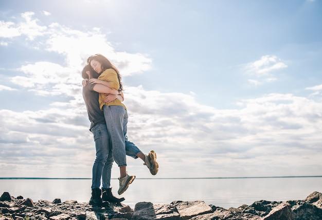 愛と旅行。湾を背景にカップルが立っています。男と女が石の上で川や海の近くに立って抱きしめています。