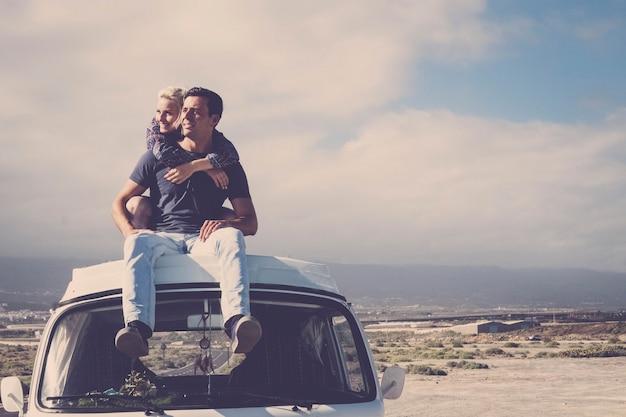 낭만적 인 방랑벽 젊은 부부와 함께 사랑과 여행 로맨스와 관계를 즐기는 오래된 빈티지 밴 옥상에서 포옹하고 함께 지내십시오.