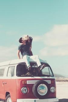 낭만적 인 방랑벽 젊은 부부와 함께 사랑과 여행을하고 로맨스와 관계를 즐기는 오래된 빈티지 밴 옥상에서 함께 지내십시오.