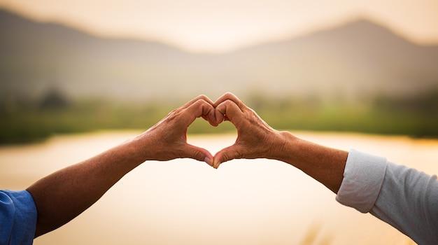 Любовь и концепция дня святого валентина. счастливая пара старших показывает знак сердца