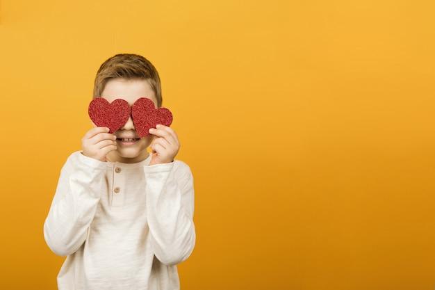 사랑과 발렌타인 데이 축하 개념. 그의 눈 앞에서 붉은 심장 모양을 잡고 어린 소년.