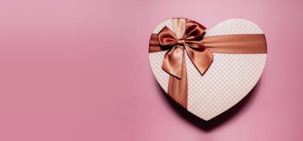 Любовь и концепция дня святого валентина. подарочная коробка в форме золотого розового сердца. вид сверху
