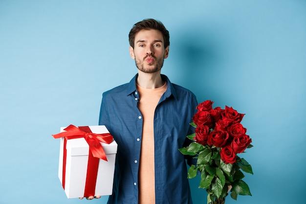 愛とバレンタインデーのコンセプト。キスのためのロマンチックなボーイフレンドのパッカー唇、青い背景の上に立って、日付に赤いバラの花束とギフトを持参してください。