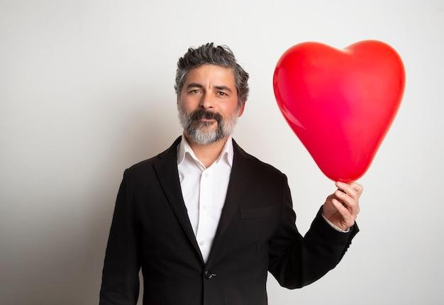 愛とバレンタインデーの男は、キュートで愛らしい孤立した笑顔の心を保持しています。赤い空気の気球を持つバレンタインの男。