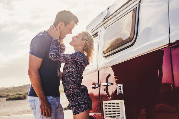 代替の若いライフスタイルの人々のための愛とヴィンテージカー-カップルと一緒に旅行を楽しむ-ガールフレンドとボーイフレンドのコンセプト-屋外で陽気で幸せ