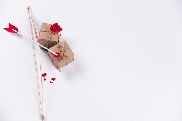 Love arrow with bow and gift boxes on table