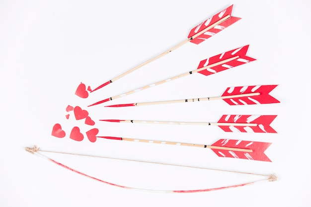 Love arrows aiming at small red hearts