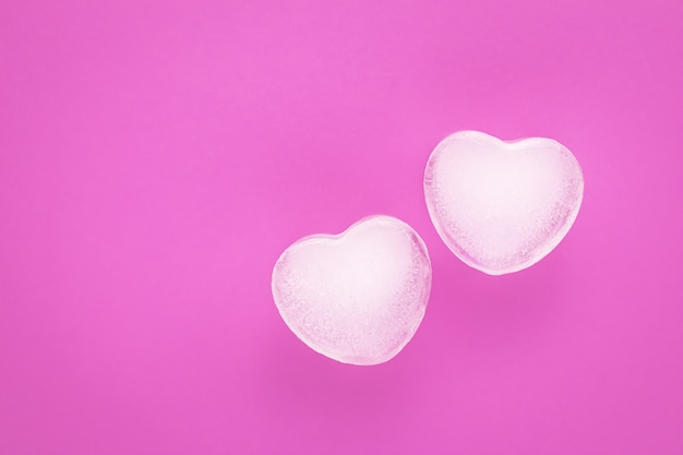 背景が大好きです。ロマンチックなピンクのカード、氷の2つの心を持つテンプレート。コピー、テキストスペース。バレンタインデーのシンボル。