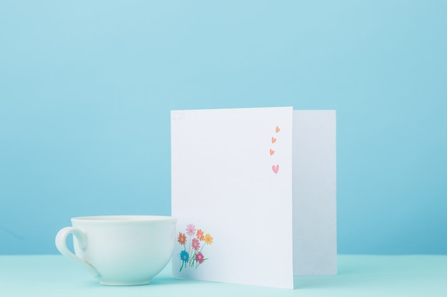 Love background with card and cup gift on table