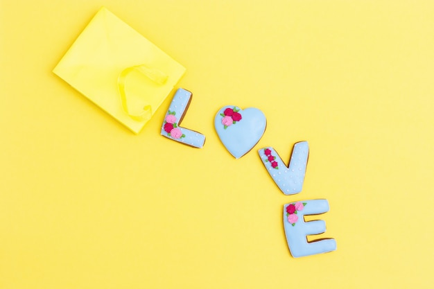 Надпись love by домашнее печенье с голубой глазурью на желтом